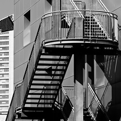 Metal staircase  and suburbs partial view B&W (suburbia) (sandroraffini) Tags: light shadows contrast suburbs urban details abstract reality newtopographics wasteland exploration bologna staircase metal industrial architecture square view canon 70200 bw black grey shades lines curves industriale architettura sandroraffini