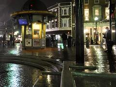Center of the Square (AntyDiluvian) Tags: cambridge reflection wet rain boston night massachusetts harvard center rainy harvardsquare kiosk middle information drizzle massave massachusettsavenue harvardcoop