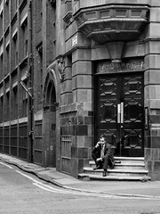 Northern Quarter #113 (Peter.Bartlett) Tags: manchester olympuspenf eyecontact wall urbanarte window unitedkingdom niksilverefex people streetphotography city doorway sitting noiretblanc doubleyellowlines cellphone peterbartlett lunaphoto man urban steps candid uk m43 microfourthirds mobilephone bw monochrome sign blackandwhite corner door architecture