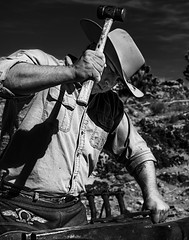 02469309-81-Farrier at Work-2-Black and White (Jim There's things half in shadow and in light) Tags: america canon5dmarkiv mikey mojavedesert nevada places redrockcanyon sigma24105mmf4dg usa cowboy horseshoer man work farrier blackandwhite
