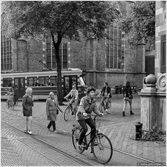Between the lines (John Riper) Tags: street people bw white black church netherlands monochrome bike bicycle john square photography mono zwartwit pavement candid streetphotography tram denhaag rails streetcar thehague htm vierkant sgravenhage straatfotografie riper johnriper