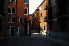 Woman on corner (Dovhage Photography) Tags: italy venice shadows light sunset back streets unknown woman walking corner escaping tourism calm tranquil orange blue door houses buildings architecture sun balcony italian flair style ramo secondo sagredo mood bellissimo