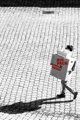 big pack (Wackelaugen) Tags: pack parcel man carry sc selectivecoloring shadow walking pavement cobles canon eos photo photography wackelaugen googlies