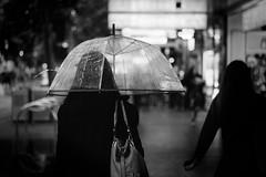 Solitude - [Seen in Explore!] (McLovin 2.0) Tags: street city urban bw white black rain night zeiss umbrella lights noir bokeh candid sony streetphotography melbourne explore 55mm explored a7s