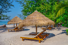 Sunbed and umbrella on Tropical beach on the island of Sihanoukville in Cambodia (marozn) Tags: beach palm honeymoon island holiday tree relax ocean coast tropical travel sand sunny enjoy summer lifestyle maldives sea resort nature vacation journey happy relaxation view palms bungalow rest hotel thailand samui paradise green asia caribbean exotic cambodia sihanoukville otresbeach outdoor calm umbrella sunbed chair lounge nobody