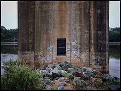 Tower Window (Firery Broome) Tags: architecture bridge footing canalbridge concrete watermarks waterlevels distressed graffiti painted stones rocks weeds window bars manmade water summitbridge summit delaware cdcanal walls concretewall paintedwall windowwednesdays newwallwednesday cellphone phonephoto iphone iphone5s iphoneography phoneography ipad ipaddarkroom apps snapseed mikecastletrail reflections waterreflections orange brown red white green gray 365