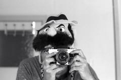 reflected self-portrait with Exakta RTL1000 camera and moustachioed hat (pho-Tony) Tags: cameraselfportraits exaktartl1000 ilfordfp4 oreston 50mm f18 oreston50mmf18 rodinal primoplan75mmf19 exakta rtl1000 rtl 1000 35mm gdr east germany german slr single lens reflex ihagee kamerawerk dresden