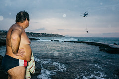 Speedos and the chopper (Spyros Papaspyropoulos) Tags: colour colourphotography color streetphotography streetphotographer street shadows light rethymno crete greece streethunters candid candidphotography ricohgr 18mm photography lightroom flash flashphotography man sea sky helicopter