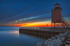 Light the Way (rdshanahan) Tags: lighthouse landscape sunset puremichigan goldenhour water rocks beauty lake longexposure orange clouds autumn fall acme charlevoix cpl beautiful summer nature upnorth magichour bluehour blue yellow michigan lakemichigan