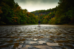 Standing on Nature's Cobblestone (iShootPics) Tags: ngc creek autumn interesting newyork foliage sony geology nature scenic ny colors pretty leaves rain gorge taughannock falls taughannockfalls man solutionpits rock landscape