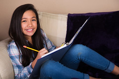 Young hispanic girl doing homework on the couch (GlobalGirl Media) Tags: education study child studying reading writing homework school kid girl childhood learning learn knowledge smart lesson notebook pencil paper schoolgirl hispanic mexican culture comfortable couch home review intelligent leader future girlpower female test exam finals happy smiling unitedstatesofamerica