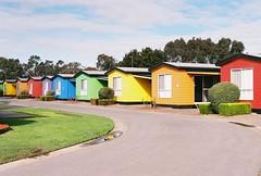 Stranded in a Rainbow (Katie Tarpey) Tags: rainbow rainbowcabins colourful colourfulcabins caravanpark cabins winter traralgon victoria film kodak kodakgold400 nikonfm10 nikkor50mm14 stranded