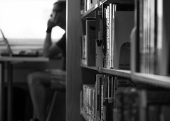 Laptops and a small library (Jan.Timmons) Tags: library libraryfuture laptop man smalllibrary blackandwhite jantimmons pacificnorthwest books shallowdepthoffield monotone