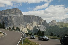 The road through Sela Pass (Vee living life to the full) Tags: italy leger travel touring holiday landscape rock pass pordoi sella towers sasspordoi mountain people nikond300 heathaze valley floor motorcycle view car park road sky cloud blue cyclists effort drive driving hairpin bend