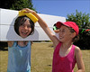 100710.051. Wet Sponge. (actionsnaps) Tags: girls friends water smiling laughing children kent sunny squeeze stocks familyfun captive fundraising margate enjoyment wethair playmates baseballcap thanet restrained charityevent summerfair pillory wetsponges northdownprimaryschool tenterdenway