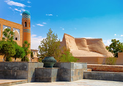 Beautiful sunny day view of ancient Itchan Kala fortress and Mosque, against the background of bright blue sky in Historic Center of Khiva (UNESCO World Heritage Site), Uzbekistan, Central Asia (n_d_14021984) Tags: world old city trip travel house building tree green tower castle tourism home stone wall architecture square asian religious temple town persian site tour place desert iran citadel muslim islam traditional famous iraq sightseeing ruin culture landmark palace unesco arabic east mausoleum national journey destination oriental orient fortification samarkand bukhara stronghold interest cultural excursion islamic urgench turkmenistan uzbek