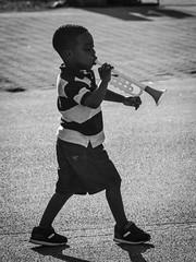 Future Miles... (tim.perdue) Tags: future miles davis trumpet toy boy child person figure street candid ohio state fair exposition center summer 2016 black white bw monochrome shadow silhouette music souvenir horn musical instrument jazz interesting interestingness explore popular explored striped shirt tennis shoes shorts plastic walking marching pavement