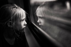 Strangers on a train. (aamith) Tags: train blackandwhite bw bnw makeportraits portrait reflection window girl nikond750 50mm sigma art sigmaart portraiture kids candid
