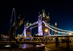 Tower Bridge and the Girl with the Dolphin fountain (Anthony Plancherel) Tags: architecture england london nightscenes nonbuilding riverthames towerbridge travel travelphotography britain greatbritain british english uk unitedkingdom nightscape lightsatnight nightphotography nighttime cityscape landmarks famousplaces fountain girlwiththedolphin stkatherinespier lightstars outdoor outside architecturephotography canon70d canon1585mm canon longexposure bridge span roadbridge road people motionblur theshard capitalcity city water pool dolphin statue drops dusk night skyline building wow