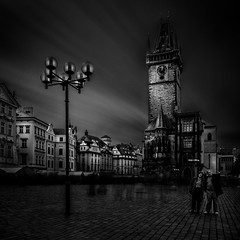 Two Tourists (One_Penny) Tags: czechrepublic prag prague praha tschechien canon6d city photography town travel urban black white blackandwhite bw fineart tourist persons people longexposure light tower architecture ndfilter square lamp oldtownsquare buildings sky clouds blur motion dark staromstskradnice townhall squareformat