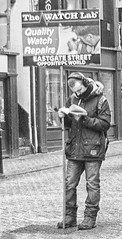 Engrossed in his work (Gill Stafford) Tags: street city england white man black advertising reading mono book cheshire image board centre center chester rows photograph gillstafford