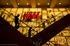 Up and Down at H&M (Edwinjones) Tags: uk red england urban color colour london yellow shop stairs photoshop dark logo photography lights photo raw photos britain sony capital perspective cities silhouettes sigma wideangle pic regentstreet clothes londres escalators hm regent shutterspeed dslra700