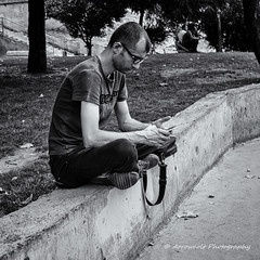Street 169 (`ARroWCoLT) Tags: streetart taksim istanbul trkiye trkei mini nxm photography dof outdoor siyahbeyaz art bw blackwhite monochrome black white blackandwhite arrowcolt nxmini pattern vintage 17mm f18 street sokak people summer samsung nx youngman young man streetphotography sitting mobile phone cellular cellphone bokeh depthoffield wall concrete park sidewalk