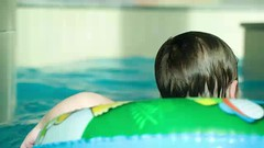 Back view of a kid swimming in rubber ring (greycoastmedia) Tags: boy people motion water pool smile swimming swim fun happy person back video kid healthy aqua child little joy device rubber ring swimmingpool health enjoy laugh bathe slider recreation activity cheerful dolly spa learn tracking active waterpark footage flotation stockvideo greycoastmedia