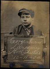 George Burn, arrested for stealing brushes and a box (Tyne & Wear Archives & Museums) Tags: wood boy portrait male face sign metal shirt scarf mouth hair screw nose newspaper interesting wire eyes hands chair child lashes skin serious head board coat 14 nail fingers victorian ears lips clothes criminal crime cap jail brushes mugshot string unusual cloth seated punishment attentive representation villains edwardian arrest stealing prisoner larceny prisoners confrontation criminals offender northshields washhouse peterjohnson neutralbackground sepiaphotograph socialheritage prudhoestreet 3shillings georgeburn 10november1902 criminalfaces northshieldspolicestation theshieldsdailynews