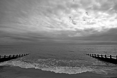 Cloudy Felixstowe (B/W) (DaveJC90) Tags: suffolk felixstowe town view landscape stone rock beach bay sea water wave waves light bright sky cloud cloudy dark shadow walk walking afternoon black white blackandwhite bw crop croped nikon d5100 digital slr camera wide angle lens 1020mm 1855mm detail sharp sharpness