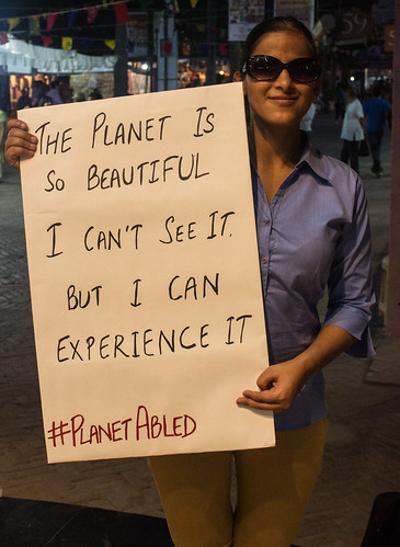 My disability doesn't stop my wanderlust: Binni, who is blind, is holding a poster saying, 'The planet is beautiful. I can't see it. But I can experience it.'