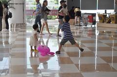 Kung Fu balloon (Roving I) Tags: boys children siblings brothersandsisters girls toddlers kungfu balloons family tiles shine reflections playing vietnam vincomcentre shopping malls danang