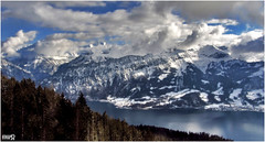 Lake Thun (VandenBerge Photography) Tags: travel blue winter sky panorama lake snow mountains alps weather clouds forest canon landscape schweiz switzerland europe view lonelyplanet snowscape winterscape berneseoberland winterbeauty lakethun cantonberne thebeautyofnature