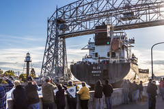 lift bridge in action (otgpics) Tags: gantry mechanical height scale ocean going vessel saltie canal park duluth minnesota crowd onlookers cameras lift bridge stern tower architecture structure shipping agriculture industry tourism maritime late afternoon fall autumn season riding high water lake superior most inland seaport