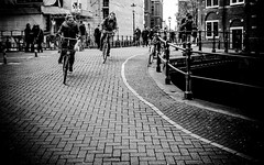 Wheels on fire (DobingDesign) Tags: street people blackandwhite netherlands amsterdam bicycle race cyclists angle bricks streetphotography racing line journey streetfurniture curve railings cycles noordholland bicycleride onyerbike