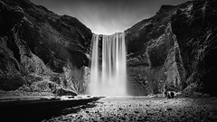 In The Presence of Skgafoss (Mabry Campbell) Tags: people blackandwhite snow ice water monochrome river dark landscape photography photo iceland rocks europe moody photographer image fav50 fav20 cliffs motionblur photograph april 100 scandinavia fav30 f71 frostbank fineartphotography skgafoss architecturalphotography skogafoss 17mm skgar fav10 southiceland fav100 fav200 ef1740mmf4lusm 2013 fav40 fav60 architecturephotography fav90 fav80 southerniceland fav70 houstonphotographer 80sec skgriver mabrycampbell april132013 201304130h6a0501 gnguleiumfimmvruhls