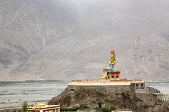 Statue of Cho Rinpoche (Crowned Buddha) looking at the Shoyok valley drenched in the rains (SaiKiranKanuri) Tags: lehtrip statue nubra monsoons karakoram range gelupa cho rinpoche crowned buddha shoyok valley rains gompa