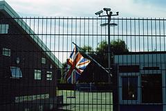 Is it a Prison? (Noah MM) Tags: nikon f801 kodacolor kodak c41 epson film analogue 35mm flag nationalism unionjack surveillance camera fence brick school urban nottingham