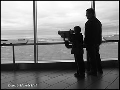 Can I Fly? - Airport X5114e (Harris Hui (in search of light)) Tags: harrishui fujix10 digitalcompact fuji fujifilm vancouver richmond bc canada vancouverdslrshooter pointshoot airport vancouverinternationalairport viewingplatform kid family dad fatherandson silhouette light backlight candid street streetcandid mono monochrome blackwhite classic classictones viewing looking airplane frame kidtalk