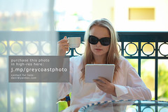 Woman sitting reading a tablet -pc on a balcony (creativemarket.photo) Tags: morning summer vacation people woman cup coffee girl sunglasses mobile modern breakfast digital computer table relax outdoors reading hotel glasses early pc portable technology tea drink terrace balcony curtain working drinking pad screen device resort communication blond sit blonde attractive wireless electronic tablet tab touchscreen touchpad ipad workingathome ipadair