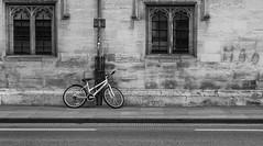 Bike (scarlet-pimp) Tags: oxford oxforduniversity bicycle university monochrome parallellines alone nikcollection mono lone silverefexpro2 blackandwhite architecture oxfordshire highstreet star