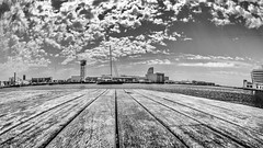 Barcelona Boardwalk (derek.dpr) Tags: barcelona boardwalk spain espana spanish waterfront riverside skyline sky clouds olympus omd fisheye fish low bw black bianco nero noir monochrome mono em10