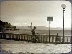 The Man and The Sea ... (MargoLuc) Tags: liguria italy landscape sea sunlight backlight man looking thinking walk bike lungomare vintage feeling bw timeless texture skeletalmess seascape mountain light shadows old sepia