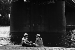 Two hats leisure (tomavim) Tags: hat water river embankment couple paving plasticcup chatting