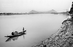 A Sigh for Kolkata (Jobopa) Tags: city travel bridge people urban blackandwhite bw india mist reflection water monochrome fog river landscape asian outdoors boat asia surf sailing ship quiet empty indian transport rep citylife cities documentary surfing calm shore sigh sail dailylife oriental kolkata calcutta reportage ganges asiatic bengali westbengal howrah generalview calcuta hooghly 2011 hoogli hugli asighforkolkata