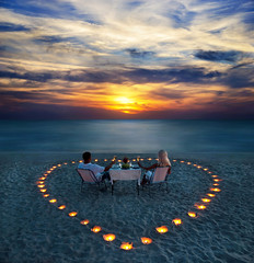 A young couple share a romantic dinner on the beach (hovi_69) Tags: trip travel family wedding light sunset sea summer vacation people woman sun holiday man love beach beautiful beauty dinner table relax outdoors happy evening sand couple paradise honeymoon day candle view heart young marriage tourist valentine romance exotic together harmony sit romantic supper concept proposal bliss valentinesday unbelievable luxurious blissful