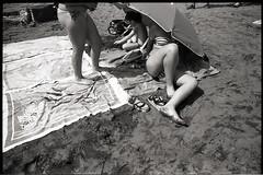 (Stars & Stripes) (Robbie McIntosh) Tags: leicamp leica mp rangefinder streetphotography 35mm film pellicola analog analogue negative leicam analogico blackandwhite bw biancoenero bn monochrome argentique autaut dyi selfdeveloped filmisnotdead fomapan100 foma fomapan 100 stranger elmarit leicaelmarit28mmf28iii elmarit28mmf28iii 28mm arsimagofd beach summertime onthebeach lidomappatella mappatellabeach swimsuit bathers umbrella women girls legs starsandstripes bikini towel