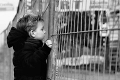 Little Boy standing (d_t_vos) Tags: street boy portrait blackandwhite face standing fence outside hands gate alone dof child hand coat watching streetphotography seethrough shawl schwarzweiss littleboy streetview noireetblanc crushbarrier 20vanalphen dickvos dtvos