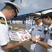 160812-N-PD309-068 QINGDAO, China (August 12, 2016) Sailors from the People's Liberation Army (Navy) North Sea Fleet present a photo album to Cmdr. Justin Harts, commanding officer of the Arleigh Burke-class guided-missile destroyer USS Benfold (DDG 65),