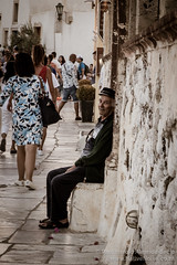 An Old Man Watches Tourists Pass in Oia, Santorini